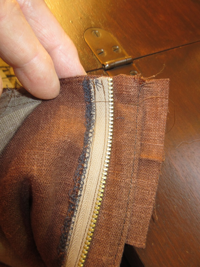 Stitching between the zipper teeth, right up to the end of the pants, but not onto the seam allowance at the end of the waistband