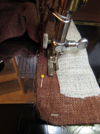 The needle aligned with the previous stitching, going towards the end of the waistband